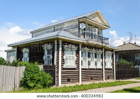 Beautiful wooden house with a mezzanine and white carved windows, sunny summer day - stock photo