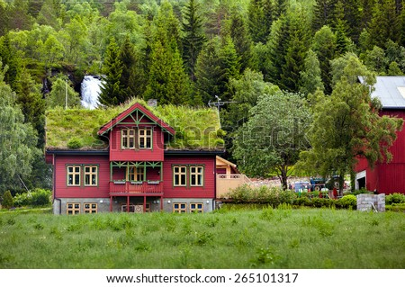 Beautiful wooden house with grass on the roof in Norway in cloudy weather - stock photo