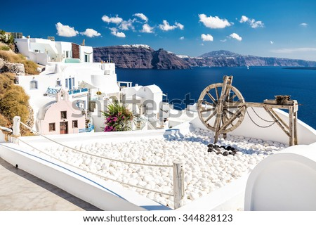 Beautiful wooden old tool as a decoration on a terrace with white houses and blue sea and sky in Oia, the most beautiful village of Santorini island in Greece - stock photo