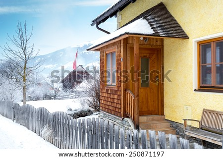 Beautiful wooden porch covered by snow in Austrian Alps - stock photo