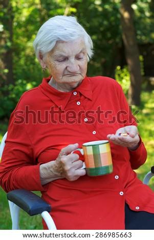 Beautiful wrinkled elderly woman taking prescription medicine - stock photo