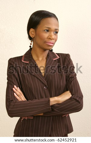 Beautiful 25 year old african american woman against office wall. - stock photo