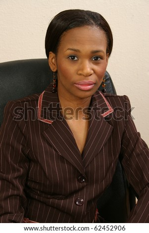 Beautiful 25 year old african american woman in suit portrait in office chair. - stock photo