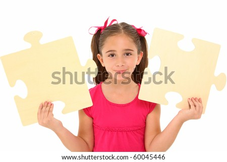 Beautiful 7 year old girl holding two large puzzle pieces over white background. - stock photo
