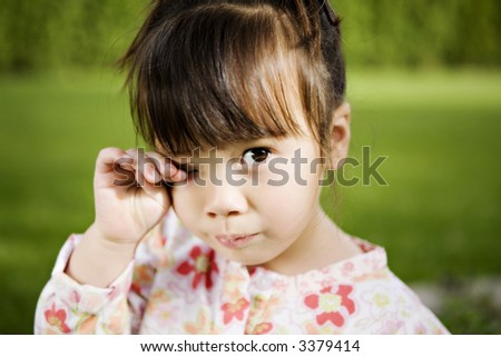 Beautiful 3-Year-Old Girl with a Sad Expression in her Backyard - stock photo