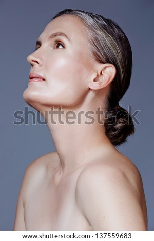 beautiful 40 year old woman with natural makeup and healthy skin texture on gray studio background - stock photo