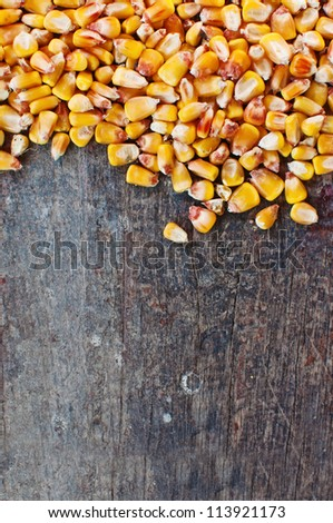 Beautiful yellow corn kernels  on a wooden table. - stock photo