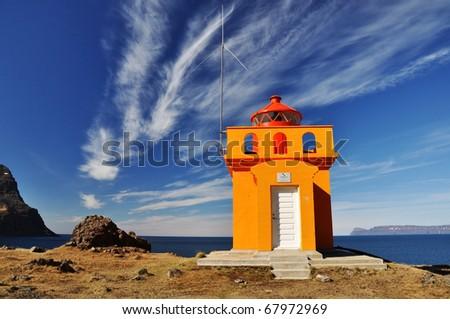 Beautiful yellow lighthouse, with the Atlantic surface as a background, West fjords, Iceland - stock photo