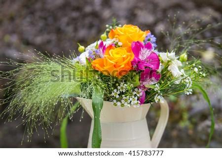 Beautiful yellow rose, pink alstroemeria, wax flower, white spray rose, green foliage flower arrangement in a jug. Wedding decor. Outdoor table decor. Vintage. Background. - stock photo