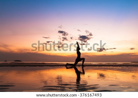beautiful yoga exercise on the beach at sunset, fitness background with copyspace - stock photo