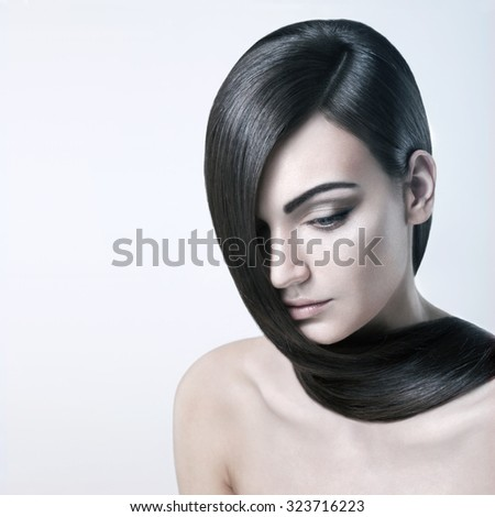Beautiful yong woman with healthy skin and well groomed hair. Her hair runs on nude shoulders and she looks tranquil. - stock photo