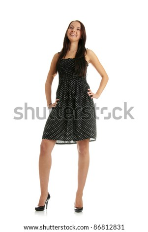 Beautiful young adult female in black dress posing in studio - stock photo