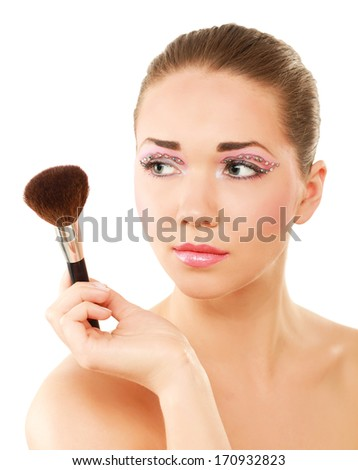 Beautiful young adult woman holds the make-up brushes near attractive face - stock photo
