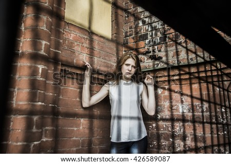Beautiful young adult woman in white dress posing holding metal mesh. Sad eyes. Hand holding on chain link fence - stock photo