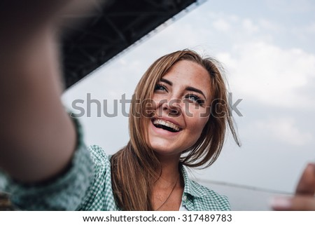 beautiful young adult woman taking picture of herself and laughs, selfie. - stock photo