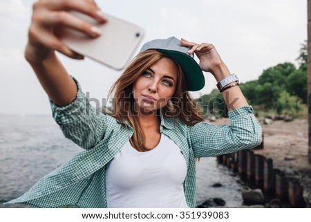beautiful young adult woman taking picture of herself, selfie. She hold cap on her head - stock photo