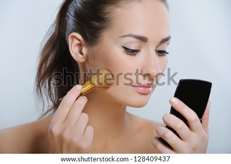 Beautiful young adult woman with healthy skin applying cosmetic on your face - stock photo