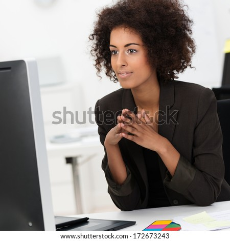 Beautiful young African American businesswoman sitting at her desk reading information on her computer monitor - stock photo