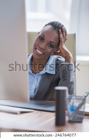 Beautiful young african american businesswoman working on computer at office - stock photo