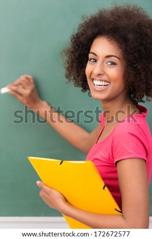 Beautiful young African American student with an afro hairstyle and vivacious smile holding a file and writing on a blackboard - stock photo