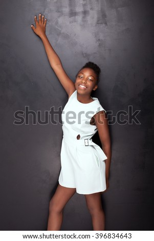 Beautiful young african american teenage girl posing in studio, looking at camera. Elegant style. Black background. - stock photo