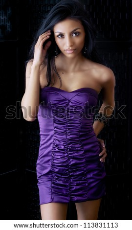 Beautiful young African American woman wearing purple dress against black background. - stock photo
