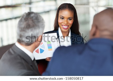 beautiful young african businesswoman explaining graph to business team - stock photo