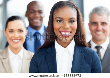 beautiful young african businesswoman with colleagues on background - stock photo