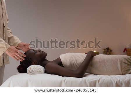 Beautiful young african woman at a spa salon laying on the couch and getting massage - stock photo