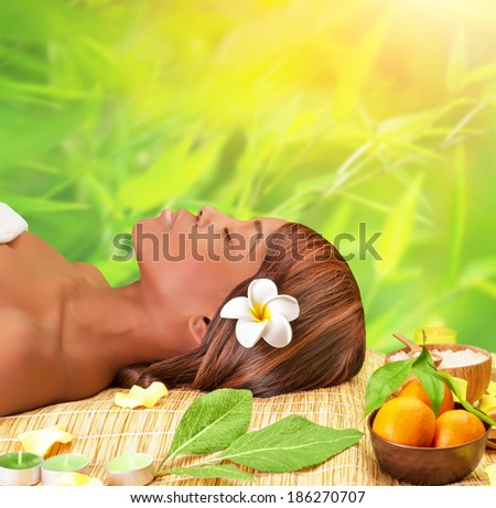 Beautiful young african woman enjoying day spa, lying down on massage table with closed eyes, take medical treatment outdoors, luxury spa resort - stock photo