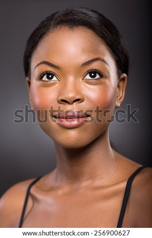 beautiful young african woman looking up on black background - stock photo