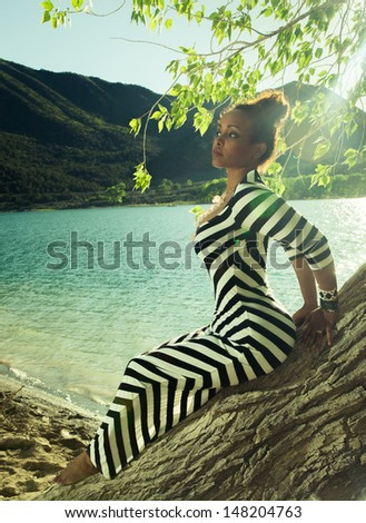 Beautiful young african woman posing on a tree trunk on a sandy seashore in a striking black and white striped dress backlit by the sun - stock photo