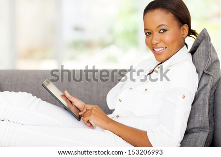 beautiful young african woman using tablet computer at home - stock photo