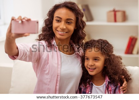 Beautiful young Afro-American mother making a photo with her cute little daughter. Both smiling. - stock photo