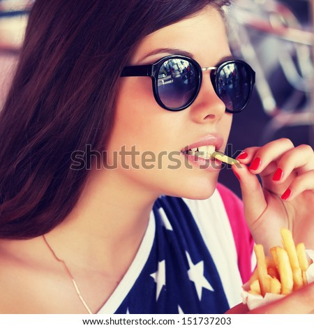 Beautiful young american girl eating french fries - stock photo