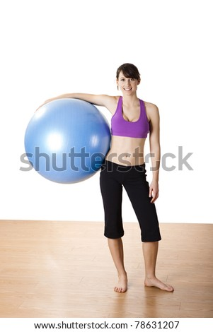Beautiful young and athletic woman making exercises on a fitness ball - stock photo