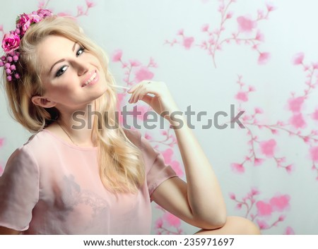 Beautiful young and sexy sensual blond glamorous girl over pink flowers background and wreath in her hair. - stock photo