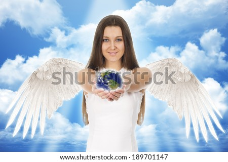 beautiful young angel woman holding Earth in hands with clouds - stock photo