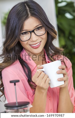 Beautiful young Asian Chinese woman or girl in geek glasses at home in her kitchen smiling and drinking a cup or mug of coffee - stock photo