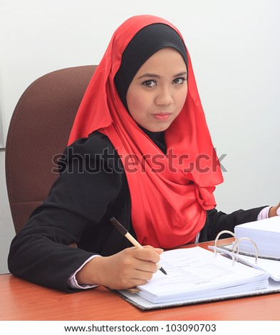 Beautiful young asian muslim business woman with serious face looking to the camera - stock photo