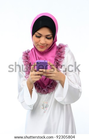 Beautiful young asian muslim woman messaging on mobile phone isolated white background - stock photo