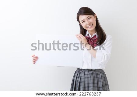 Beautiful young asian school girl holding blank white board - stock photo