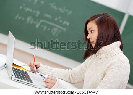 Beautiful young Asian student hard at work sitting at her desk in the classroom using a laptop computer, side view - stock photo