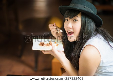Beautiful young asian student woman drinking coffee and eat bakery,smiling in cafe. - stock photo