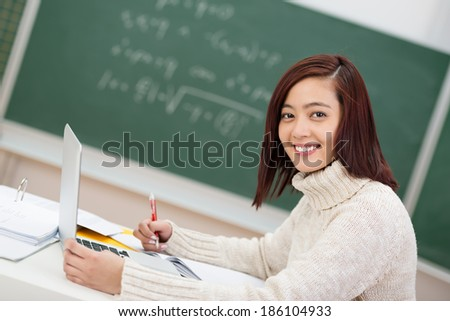 Beautiful young Asian university student sitting in class working on her notes and turning to smile at the camera - stock photo