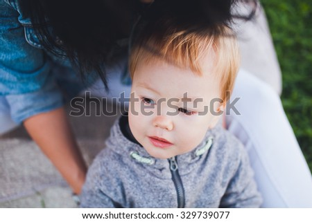 Beautiful young asian woman and her son outdoors. Mother with dark hair and son is blond. Unusual appearance and heredity concept. Boy looking aside while mom hugs him. Toned photo. Overhead view - stock photo