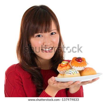 Beautiful young Asian woman holding a plate of cakes and breads isolated on white background - stock photo