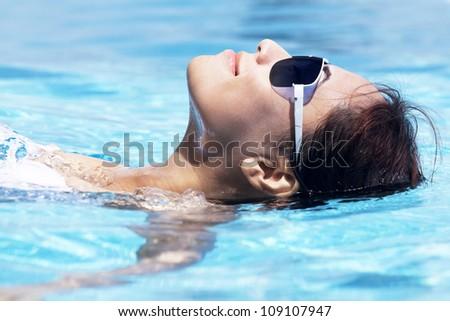 Beautiful young asian woman resting in the swimming pool on the sunny day - stock photo