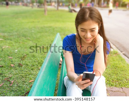 Beautiful young Asian woman smiling when looking on cellphone at sunset scene (soft focus and selective focus on smiling face with blurry background of park) - stock photo