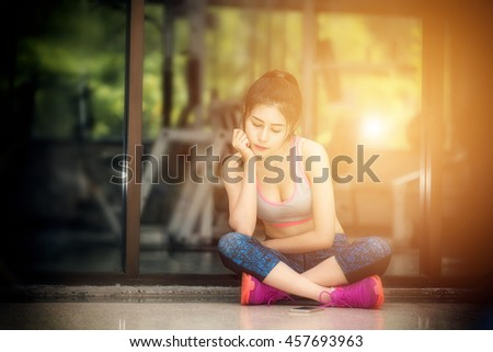 Beautiful young asian woman waiting her boyfriend calling in front of fitness office, vintage tone of photography with morning sunlight effect. - stock photo